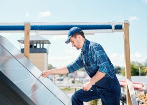 Young technician master in workwear bending over solar panel on the roof while adjusting handle